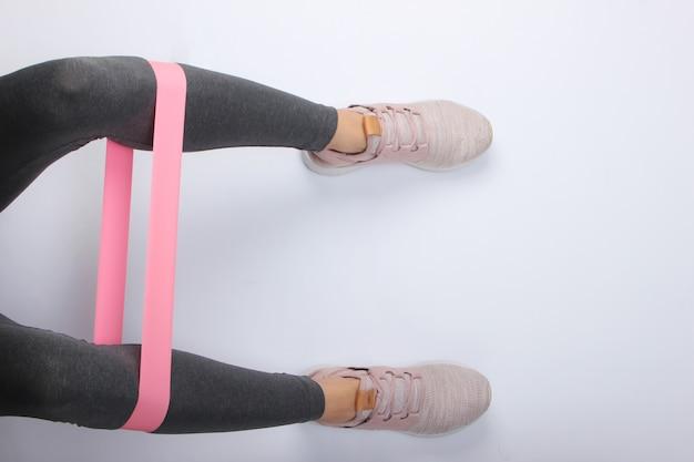 Piedini femminili in leggings sportivi e scarpe da ginnastica facendo esercizi con elastico fitness su superficie bianca. vista dall'alto
