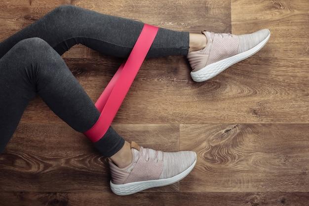 Piedini femminili in leggings sportivi e scarpe da ginnastica facendo esercizi con elastico fitness su un pavimento di legno. allenamento fitness a casa. vista dall'alto