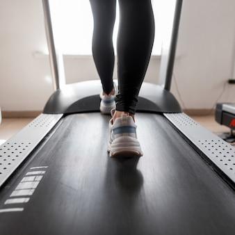 Piedini femminili in scarpe sportive in palestra. donna che corre sul tapis roulant