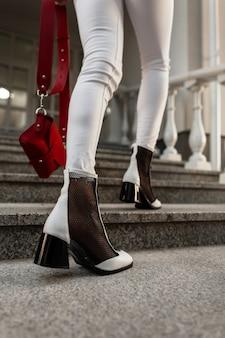 Gambe femminili in eleganti jeans bianchi con una borsa in scarpe eleganti per strada. vista dall'alto.