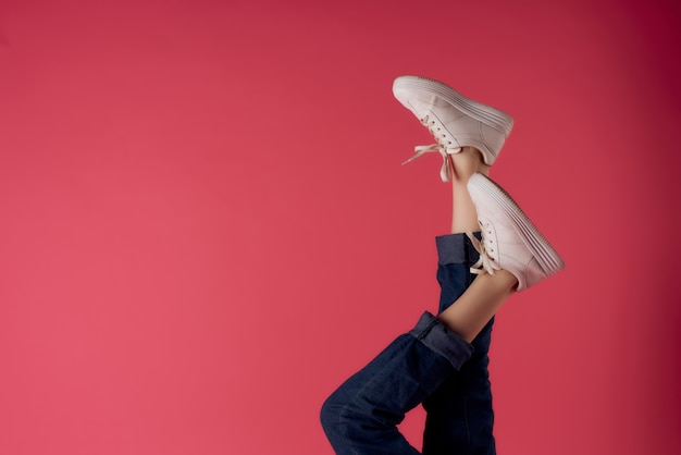 Gambe femminili capovolte in scarpe da ginnastica bianche sfondo rosa moda
