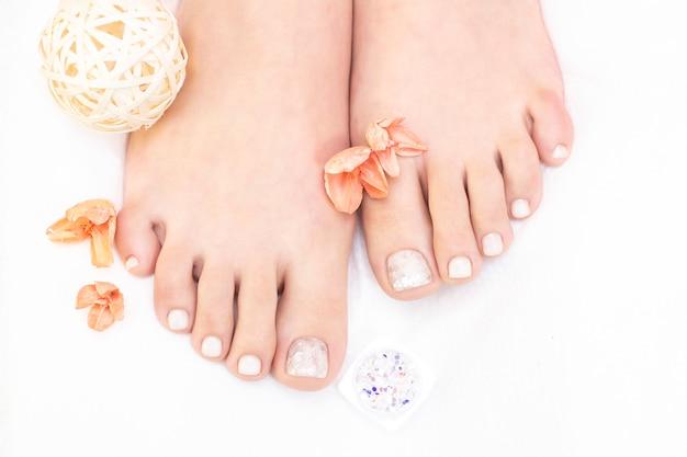 Piedini femminili su sfondo bianco. le unghie hanno un aspetto fresco e ordinato durante la procedura di pedicure.