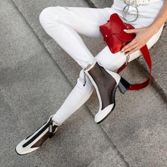 Gambe femminili in jeans bianchi con una borsa rossa e scarpe alla moda siedono per strada