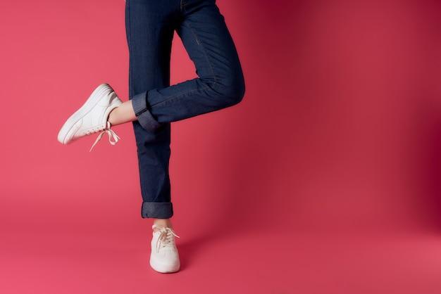 Gambe femminili in scarpe da ginnastica bianche in posa di moda sfondo rosa