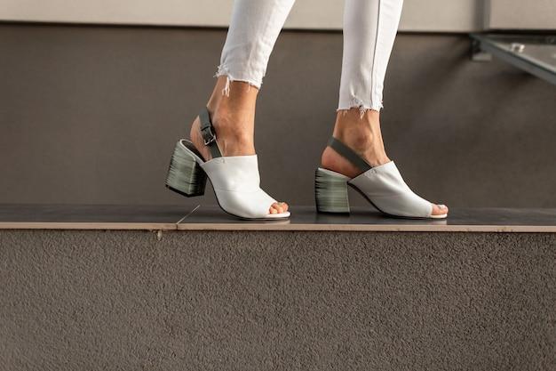 Le gambe femminili con le scarpe bianche estive alla moda camminano vicino al muro grigio