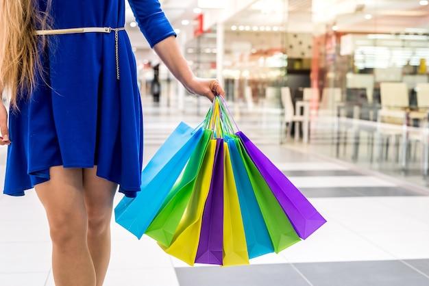 Gambe femminili con borse da imballaggio in centro commerciale