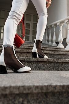 Gambe femminili con una borsa rossa in jeans bianchi e scarpe di cuoio all'aperto sui gradini