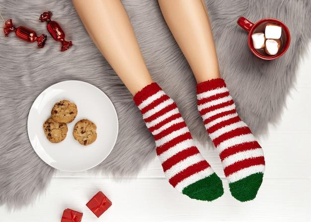 Gambe femminili con unghie rosse e tazza di cioccolata calda su una soffice coperta grigia