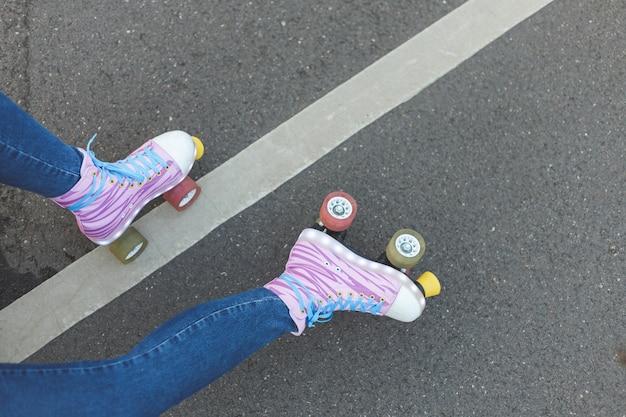 Gambe femminili con i pattini a rotelle sulla vita attiva della via di concetto di vista superiore del fondo dell'asfalto
