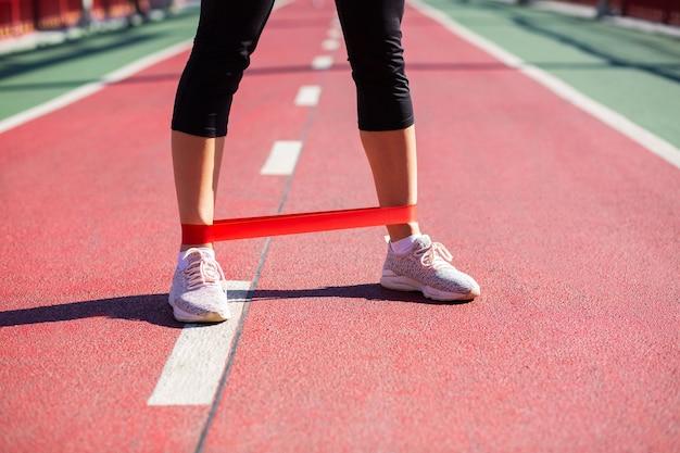 Gambe femminili con fascia di resistenza in gomma. colpo all'aperto