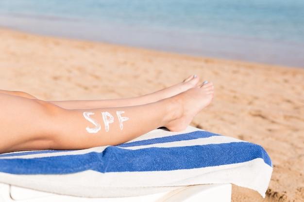 Gambe femminili con parola spf fatta di crema solare in spiaggia. concetto di fattore di protezione solare.