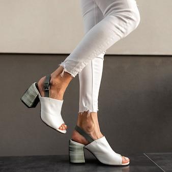 Gambe femminili con eleganti jeans bianchi e scarpe estive in pelle alla moda vicino a un edificio vintage sulla strada. avvicinamento.