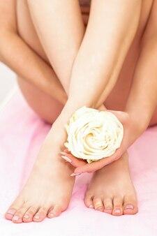 Piedini femminili con una rosa bianca in mani femminili, seduto su un divano in un centro termale di bellezza