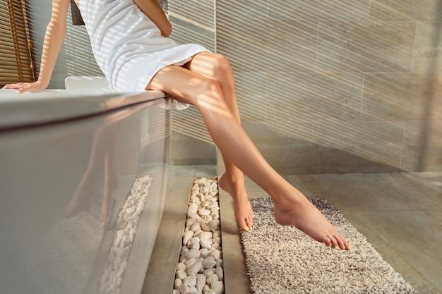 Piedini femminili con unghie gialle in bagno con luce solare