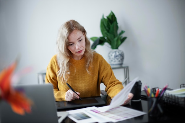 Designer di logo femminile che lavora sul suo tablet collegato a un laptop