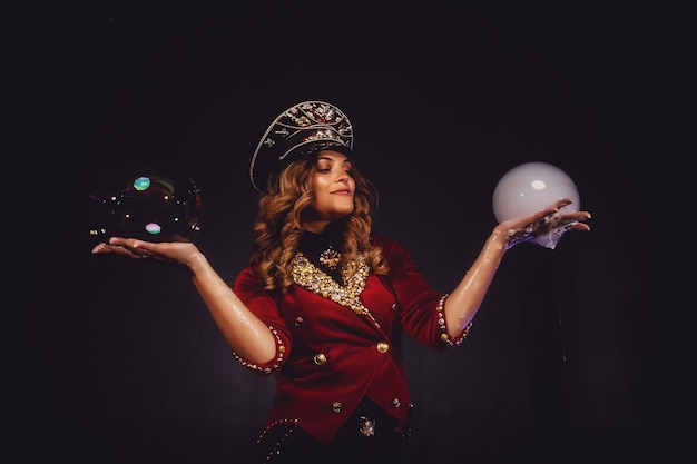 Il mago femminile fa spettacolo con bolle di sapone, un illusionista in abiti teatrali, su sfondo nero black