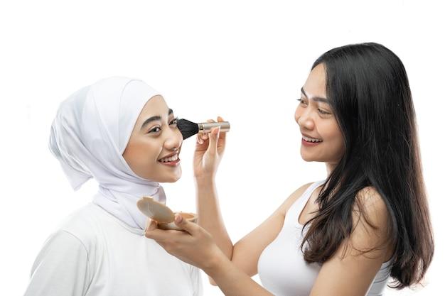 Truccatore femminile che applica guancia con pennello di giovane donna musulmana in hijab