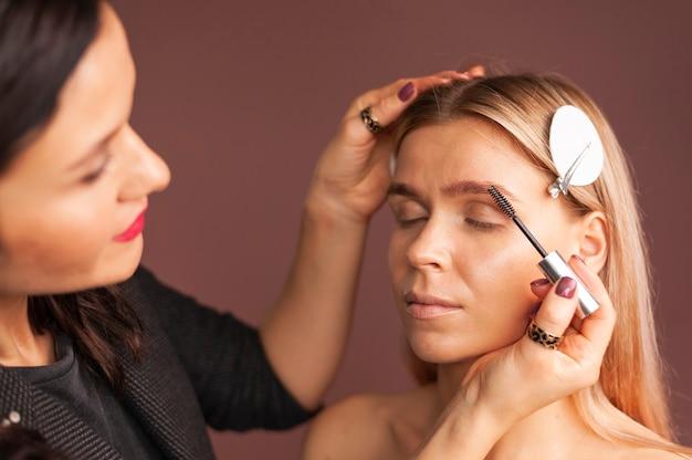 Il truccatore femminile porta le sopracciglia della giovane donna con la spazzola professionale