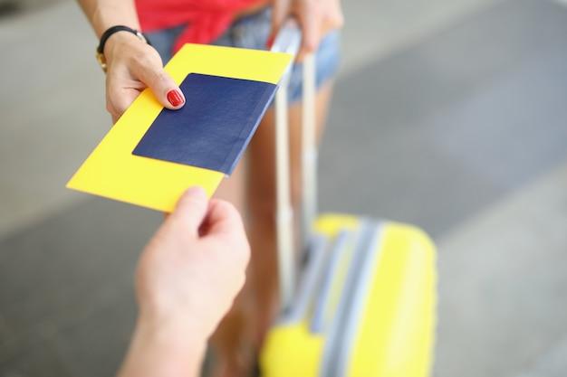 Passaporto e biglietto della stretta della mano maschio femminile su priorità bassa della valigia