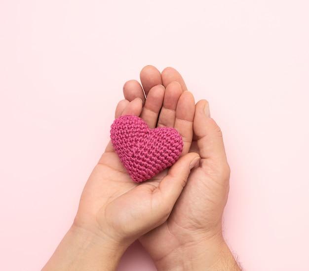 Mano femminile e maschile che tiene un piccolo cuore rosso lavorato a maglia, la donazione e il concetto di aiuto