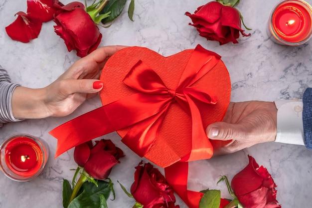Donne e uomini regalano una scatola rossa a forma di cuore con un fiocco di raso circondato da rose e candele