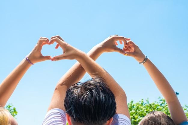 Mani femminili e maschili a forma di cuore, sullo sfondo di alberi e un parco estivo. simbolo di amore, fiducia