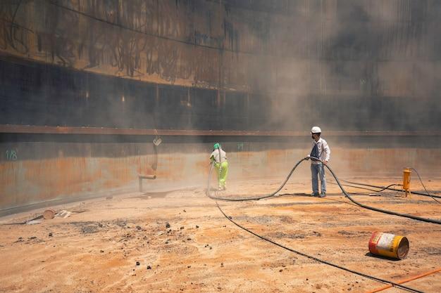 Preparazione della piastra di corrosione superficiale del lavoratore di linea femminile e maschile mediante sabbiatura dell'olio interno del serbatoio