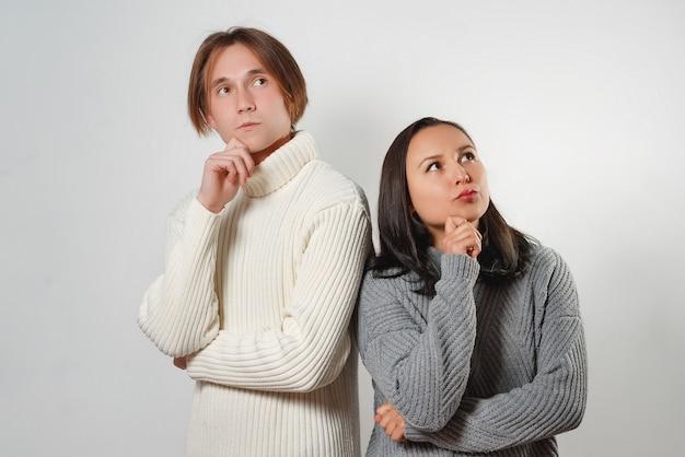 Femmina e maschio in piedi l'uno vicino all'altro con espressioni pensierose cercando di trovare una soluzione.