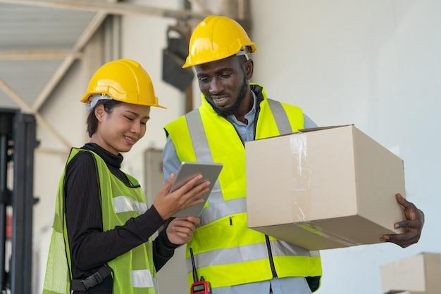 Lavoratori di sesso femminile e maschile in giubbotti di sicurezza e casco guardando tablet