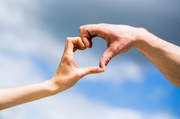 Mani dell'uomo e della donna sotto forma di cuore contro il cielo. mani a forma di cuore d'amore. cuore dalle mani su uno sfondo di cielo. la ragazza trova la mano maschile a forma di cuore ama il cielo blu. amore, concetto di amicizia
