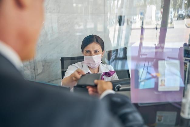 Il manager donna in maschera dietro il vetro protettivo sta prendendo i documenti del viaggiatore maschio al banco di registrazione