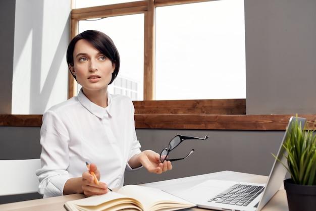 Il manager femminile nell'ufficio documenta lo sfondo chiaro del lavoro professionale