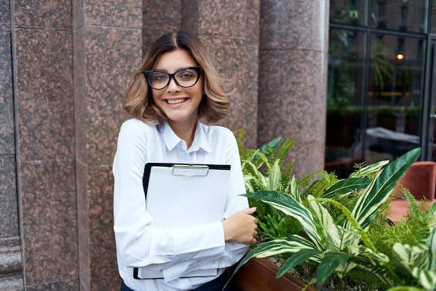 Il manager femminile all'aperto con i documenti in mano ha isolato lo sfondo