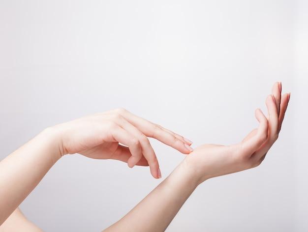 Mano femminile curata che misura gli oggetti invisibili, gesto di fabbricazione della palma della donna