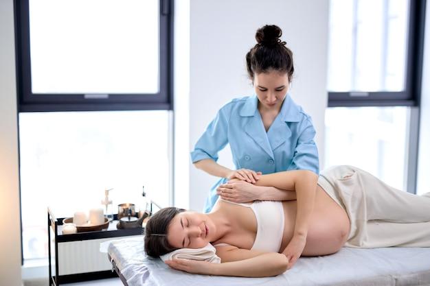 Il massaggiatore femminile massaggia il braccio e le spalle della giovane donna incinta