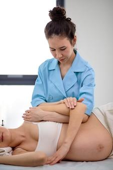 Massaggiatore femminile che muove la schiena e le braccia della donna incinta durante il massaggio nel salone della stazione termale