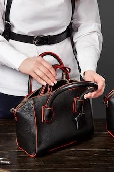 Master femminile che controlla la completezza della borsa in pelle nera
