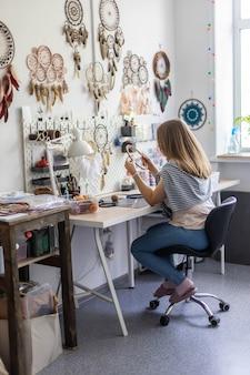 Maestro femminile che crea acchiappasogni che lavora in officina con piume e materiali