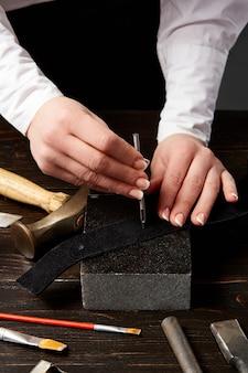 Maestro femminile che fa buchi nella tracolla della borsa in pelle