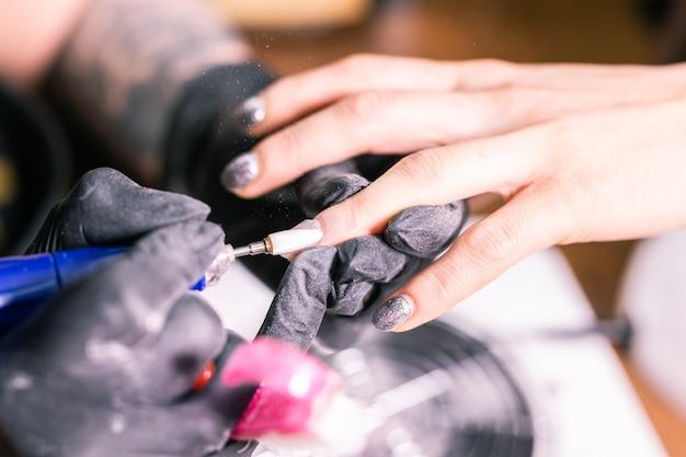 Il maestro femminile utilizza una macchina elettrica per rimuovere lo smalto durante la manicure nel salone. vicino