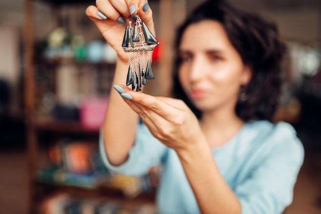 Maestro donna con pinze che fa orecchini fatti a mano