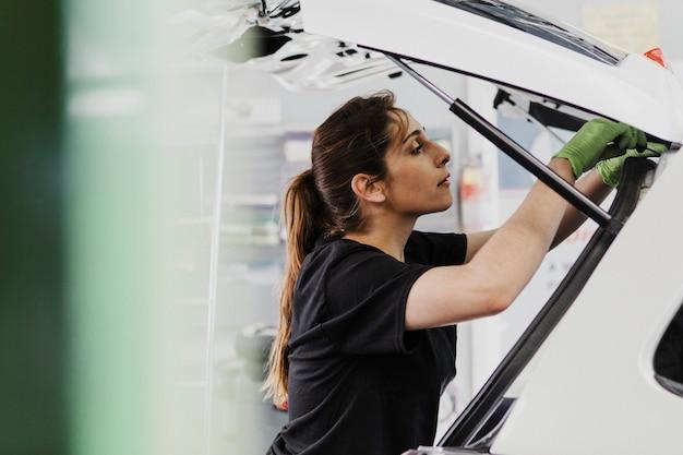 Meccanico donna che controlla il bagagliaio dell'auto