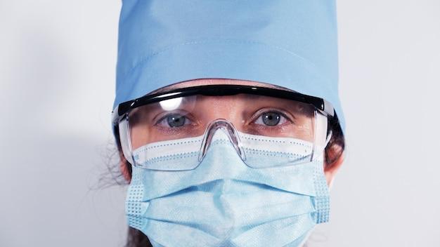 Erba medica femminile in mascherina medica eliminabile, vetri di plastica protettivi e cappuccio del tessuto, ritratto di un medico stanco con gli occhi tristi, fine su