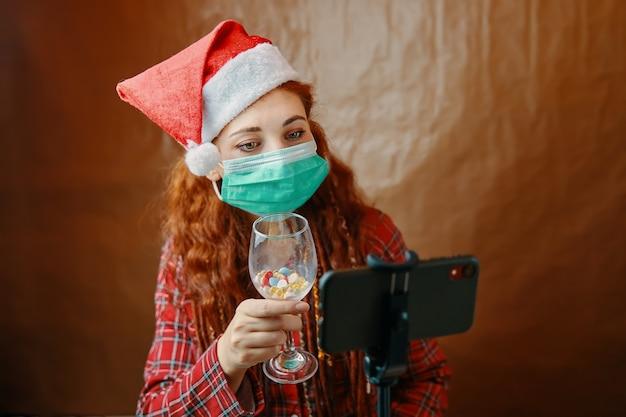 Donna in maschera medica e cappello di babbo natale con un bicchiere di pillole davanti al suo smartphone. le videochiamate di natale vengono messe in quarantena. l'umore del nuovo anno. donna dai capelli rossi con i dreadlocks.