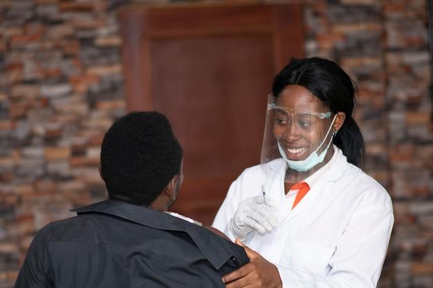 Medico femminile che sorride con un paziente che sta per ricevere un vaccino