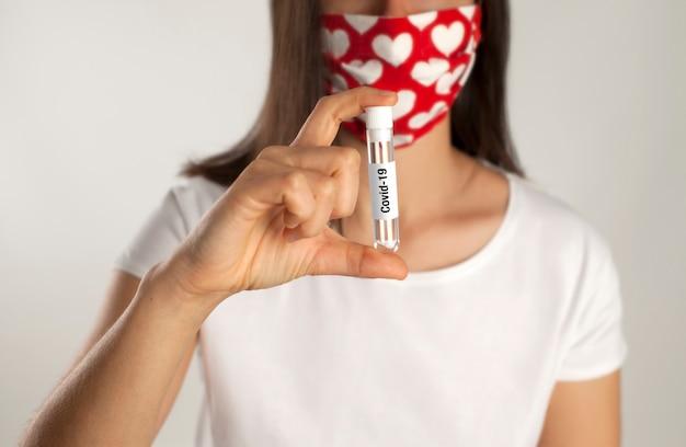 Il ricercatore medico femminile con la mascherina chirurgica tiene una provetta