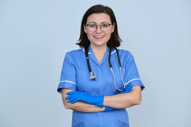 Operaio medico femminile in uniforme blu con stetoscopio e guanti, donna professionale fiduciosa con le braccia conserte che guarda l'obbiettivo, sfondo grigio chiaro