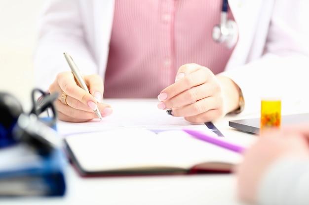 La mano del medico di medicina femminile tiene il barattolo delle pillole e scrive la prescrizione al paziente al tavolo da lavoro.