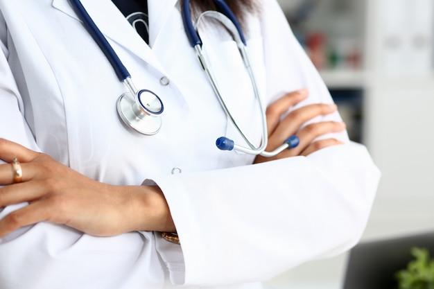 Mani di medico di medicina femminile incrociate