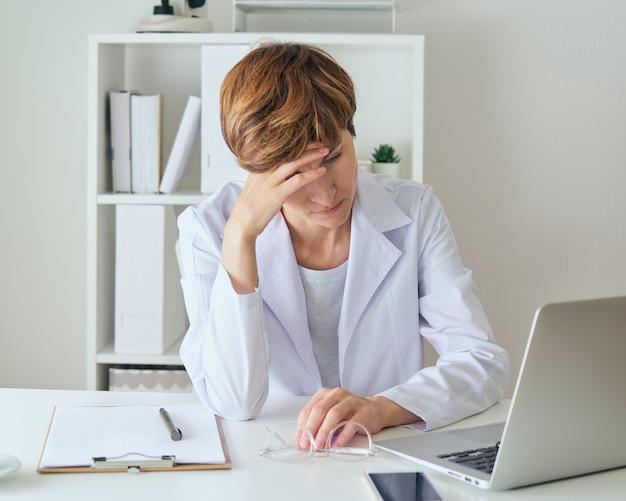 Operaio di medicina femminile che tocca l'aspetto negativo della stanchezza e della malattia della fronte del duro lavoro